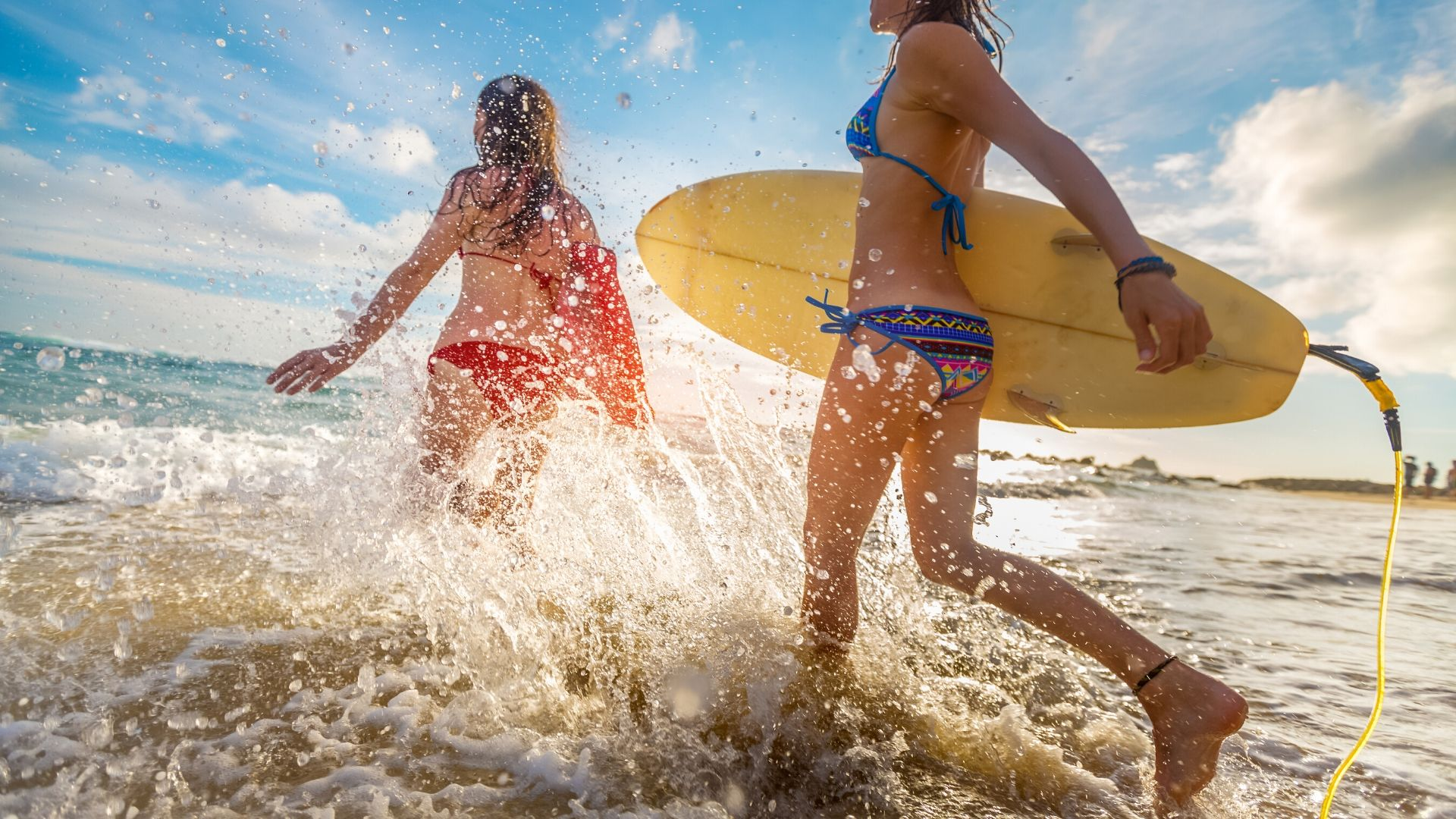 Two women running to surf
